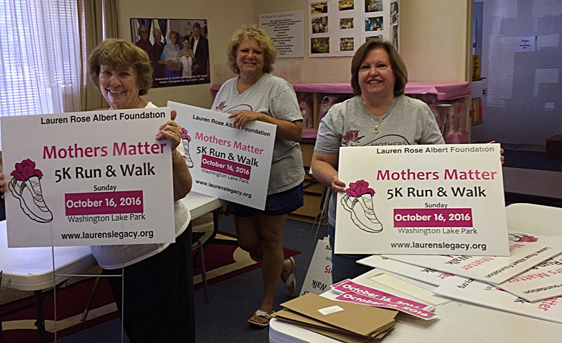 Mothers Matter team with 5K Event Signs