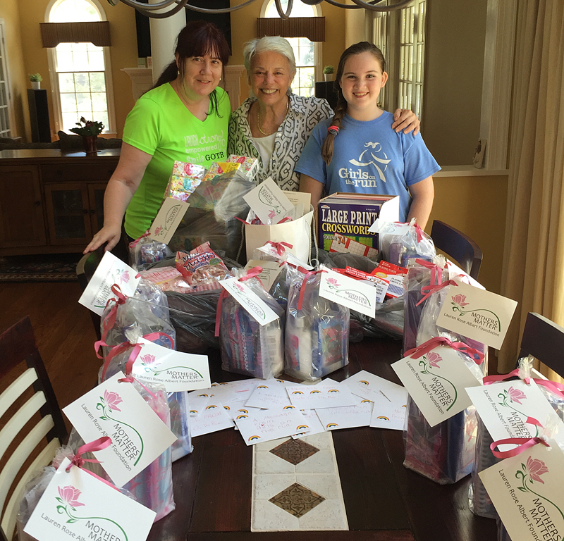 LRAF Founder & President Susan Rose picking up the Girls on Run Gift Bags